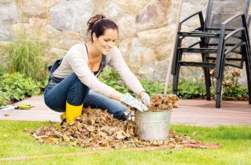Smiling woman stuffing leaves pail autumn gardening