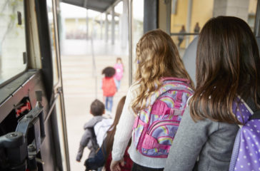 Two girls waiting behind their friends to get off school bus