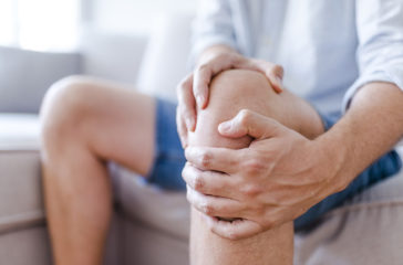 Man suffering from knee pain sitting sofa